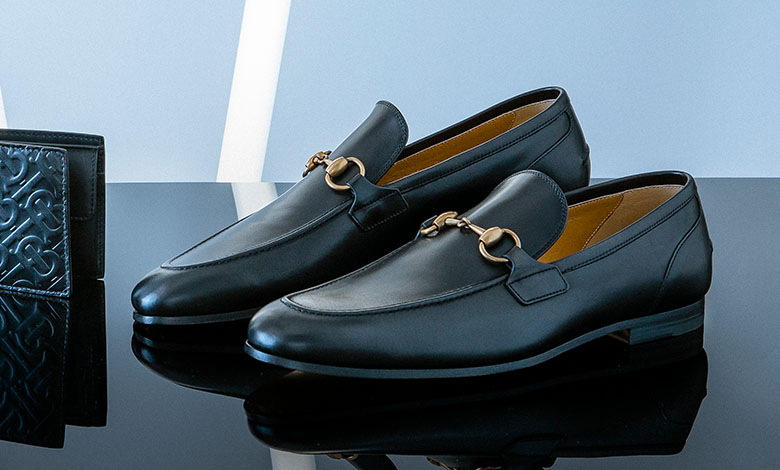 A pair of black leather Gucci horsebit Jordan loafers