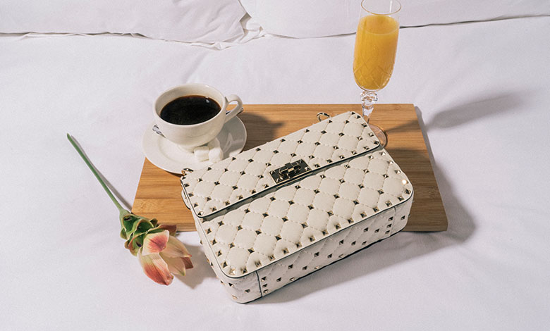 A cream leather Valentino Rockstud bag on a bed and breakfast tray on a luxurious white bed with a coffee and a glass of bucks fizz