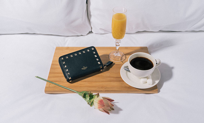 A black leather studded Valentino purse on a breakfast tray with coffee, a glass of bucks fizz and a single rose