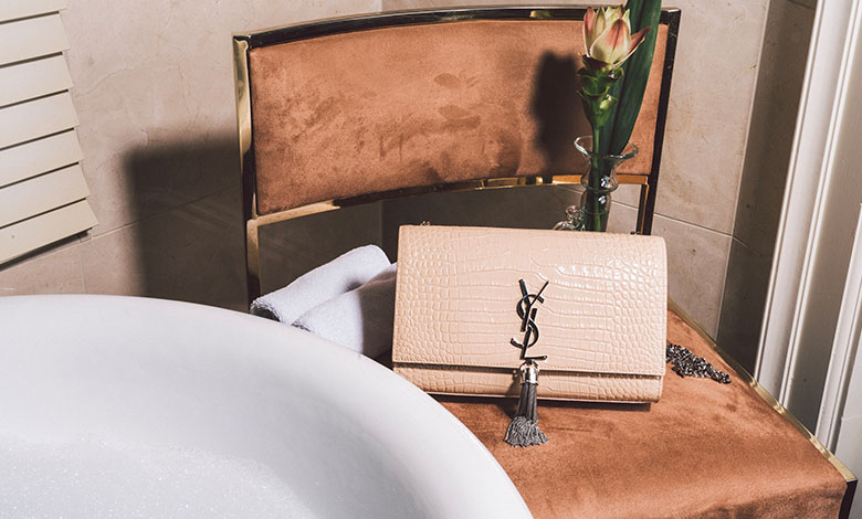 A peachy leather Saint Laurent Kate handbag with a silver chain tassel and YSL logo on a dusty pink velvet-upholstered chair next to a bubble bath