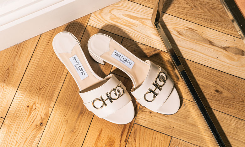 A pair of ivory leather Jimmy Choo mules with an open toe and CHOO in metal on the front