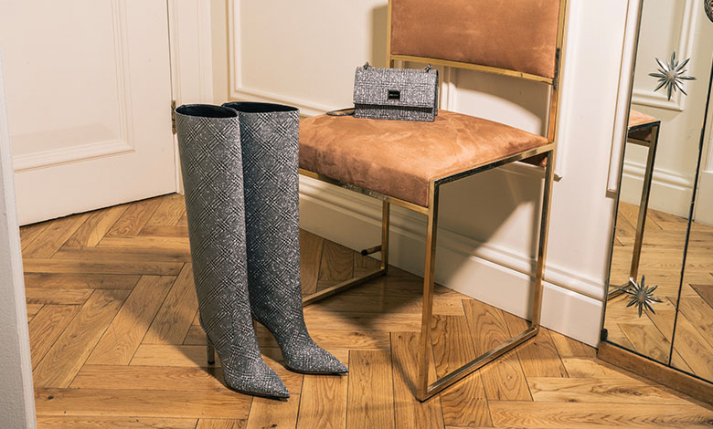 A pair of knee-high, grey, white and black checked Jimmy Choo boots with a high heel and a matching bag