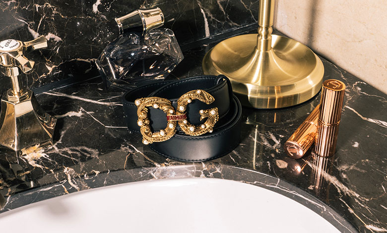 An embellished Dolce and Gabbana leather belt with a metal D&G logo buckle  in ornate gold metal with pearl studs and an enamel panel that reads Amore