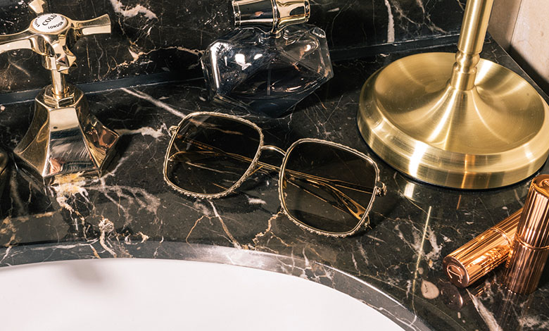 A pair of gold metal framed Alexander McQueen sunglasses on a marble surface beside a sink