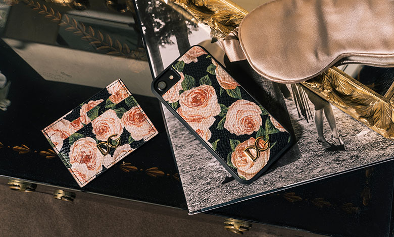 A Dolce & Gabbana black phone case and card wallet printed with pink roses and green leaves on a black glossy chest of drawers beside a mirror tray and pink silk sleeping mask.