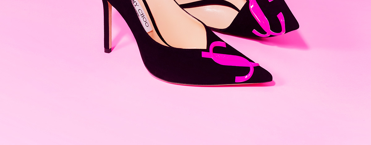 A still life image of a pair of black Jimmy Choo X FLANNELS limited edition heeled pumps with a slightly pointed toe and a pink Jimmy Choo JC logo on the toe
