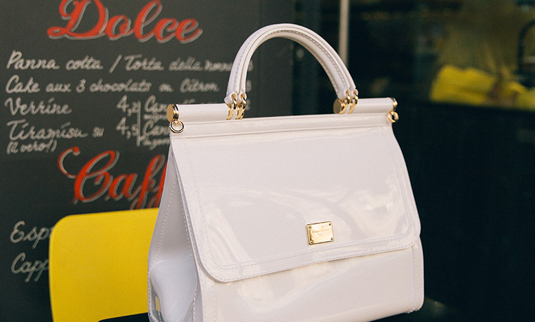 A white semi-transparent rubber Dolce & Gabbana Sicily bag on top of a cafe table
