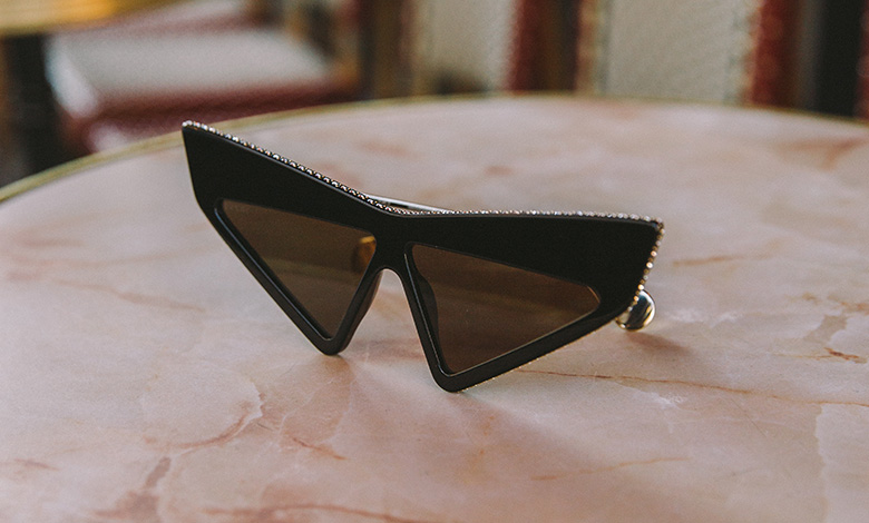 Gucci frame acetate sunglasses with diamante on a cafe table in Paris