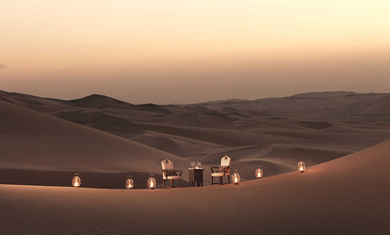 A table setting in the desert sand dunes surrounded by candles at the Qasr al Sarab Desert Resort