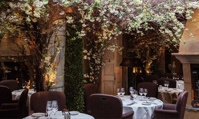 Linen-covered tables in the Clos Maggiore conservatory restaurant overhung with cherry blossoms