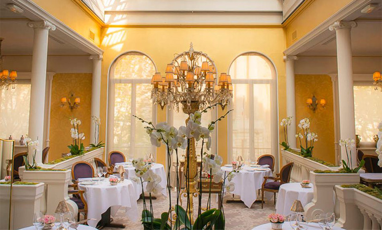 The yellow dining room with round tables and decorative lamps at Restaurant Lasserre in Paris