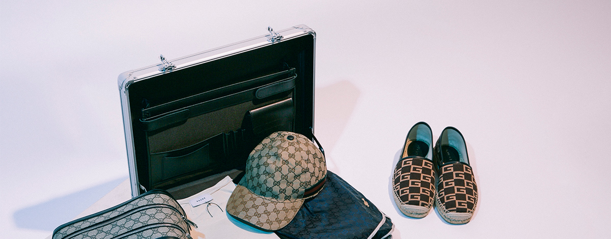 Suitcase packed with Gucci washbag, cap, navy swim shorts and brown logo espadrilles, Rhude designs logo T-shirt, Givenchy sliders and Saint Laurent sunglasses