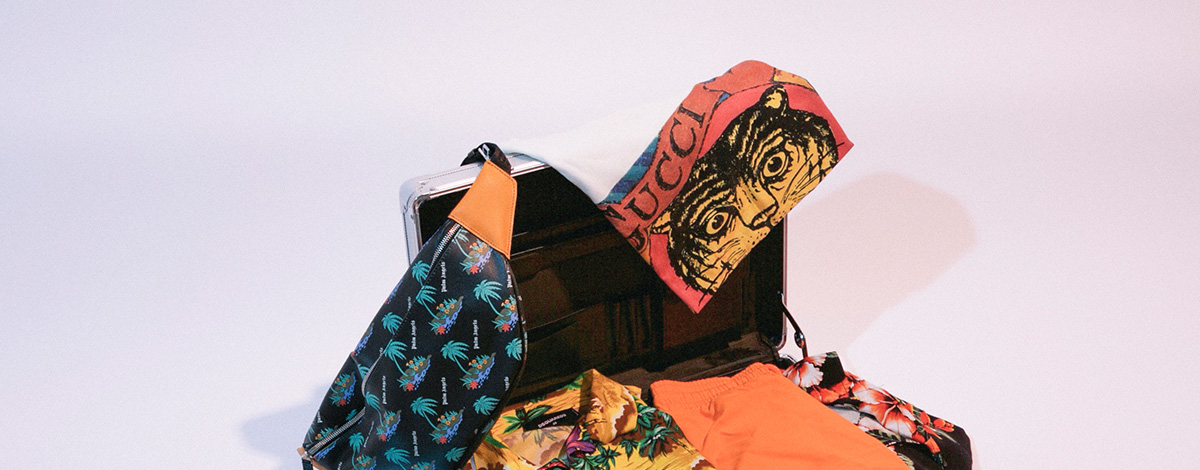 Suitcase packed with Gucci tiger face T-shirt, Palm Angels palm tree print bum bag and sliders, Dsquared2 Hawaiian shirt, Rhude Designs Hawaiian shirt, orange Vilebrquin swim shorts and vintage print Versace cap