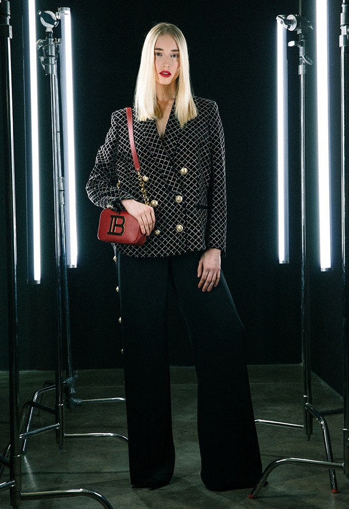 A female model wearing a black velvet glitter Balmain blazer with black wide leg Balmain trousers, black pointed toe Balmain pumps and a red leather Balmain B camer bag