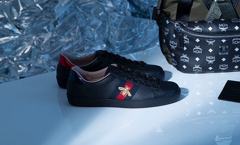 Black leather Gucci trainers with a Gucci web stripe and gold embroidered bee