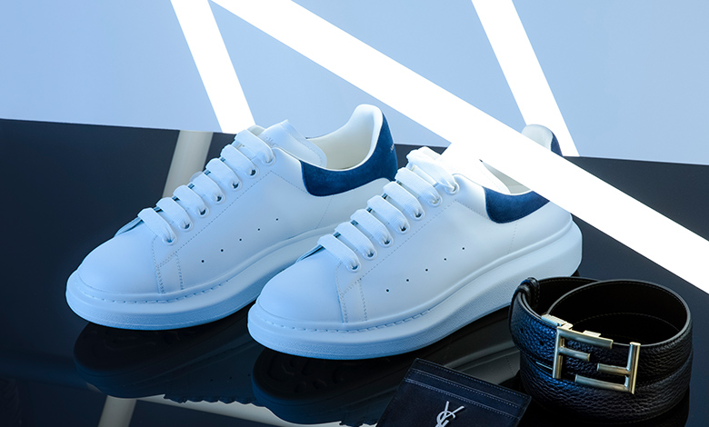A pair of white Alexander McQueen oversized trainers with a blue heel tab and logo on the tongue