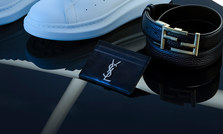 A black leather Saint Laurent card holder with a silver metal YSL logo