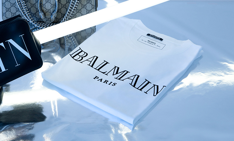 A white Balmain front logo crew neck T-shirt with a large graphic Balmain logo on the front
